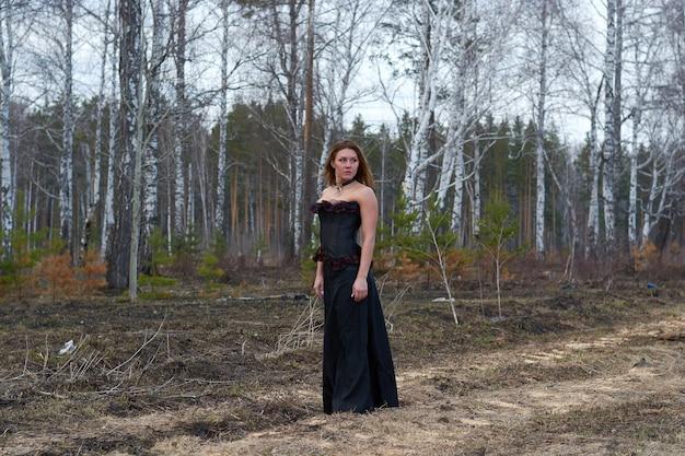 Dziewczyna w czarnej sukience w lesie. dziewczyna jest czarownicą w czarnym gorsecie.