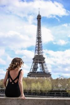 Dziewczyna w czarnej sukience z tyłu i latem patrzy na wieżę eiffla w paryżu