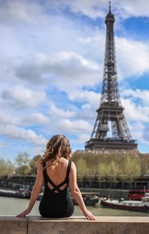 Dziewczyna w czarnej sukience z tyłu w pobliżu wieży eiffla w paryżu w lecie
