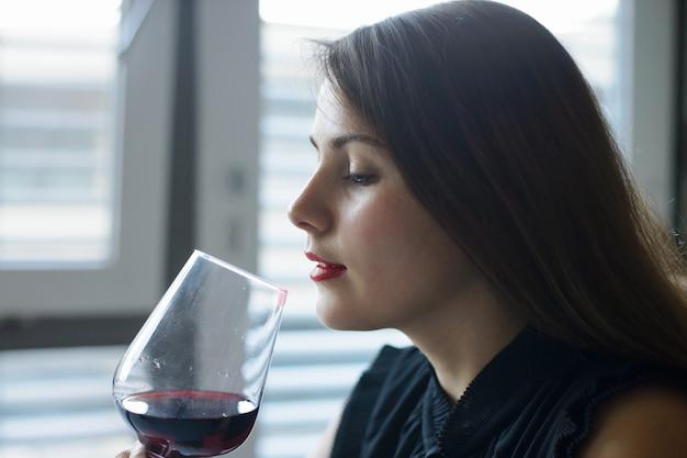 Dziewczyna w czarnej sukni, podziwiając smak czerwonego wina