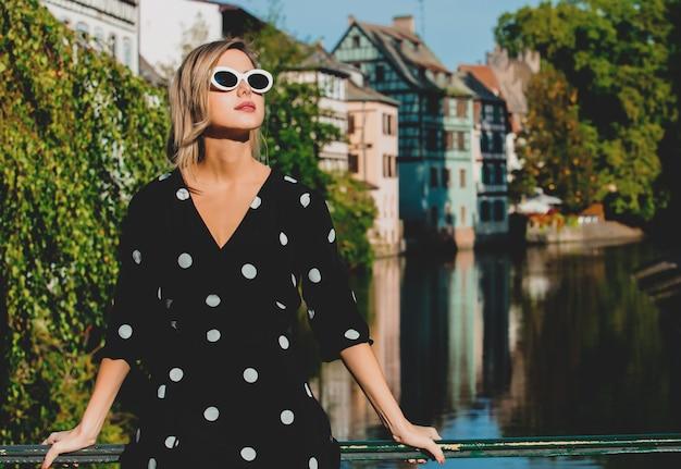 Dziewczyna w czarnej sukni pozostaje w pobliżu kanału w strasburgu