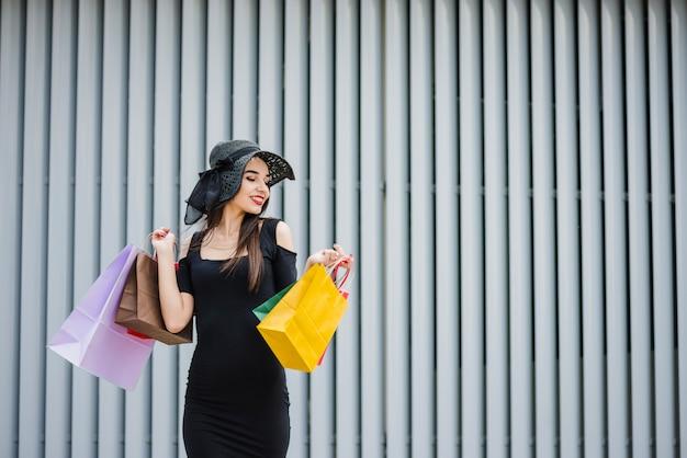 Dziewczyna w czarnej sukni przewożących torby na zakupy