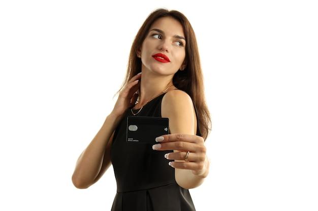 Dziewczyna w czarnej sukni z kartą kredytową na białym tle.