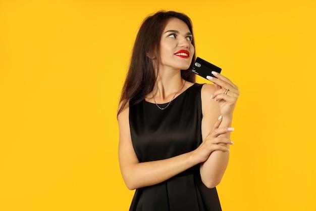 Dziewczyna w czarnej sukni z kartą kredytową na żółtym tle.