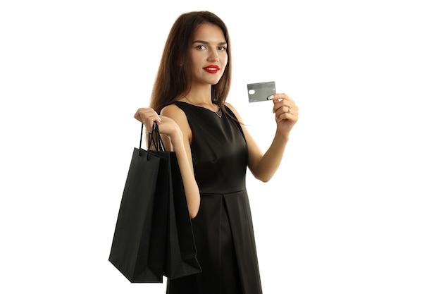 Dziewczyna w czarnej sukni z papierowymi torbami i kartą kredytową na białym tle.