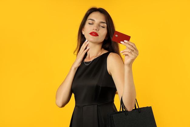 Dziewczyna w czarnej sukni z papierowymi torbami i kartą kredytową na żółtym tle.