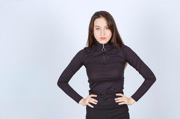 Dziewczyna w czarnych ubraniach daje profesjonalne i neutralne pozy bez reakcji.