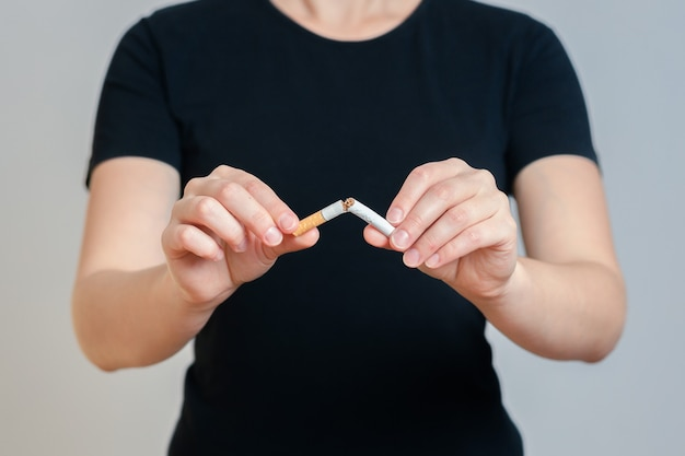 Dziewczyna w czarnych ubraniach łamie papierosa. na szarym tle. pojęcie zakazu palenia