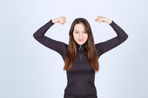 Dziewczyna w czarnych ubraniach pokazuje jej mięśnie pięści i ramion.