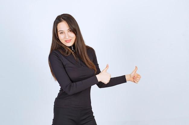 Dziewczyna w czarnych ubraniach pokazuje kciuk znak.