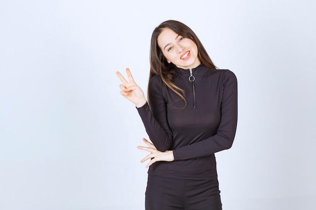 Dziewczyna w czarnych ubraniach pokazuje znak pokoju i przyjaźni.