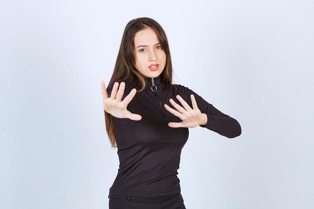 Dziewczyna w czarnych ubraniach próbuje coś powstrzymać.
