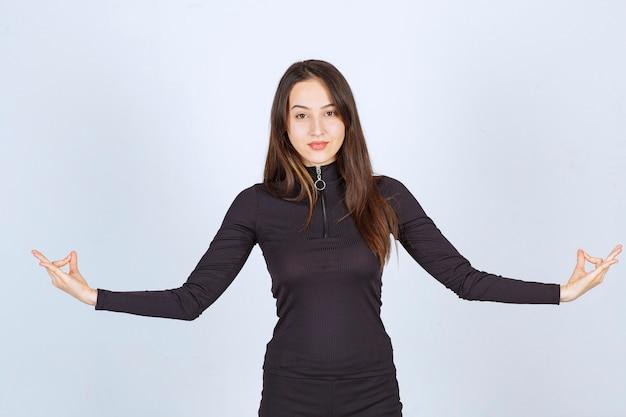 Dziewczyna w czarnych ubraniach robi medytacji.