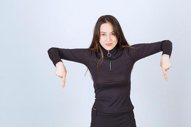 Dziewczyna w czarnych ubraniach, wskazując poniżej.