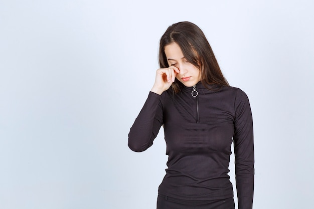 Dziewczyna w czarnych ubraniach wygląda na smutną i przygnębioną.
