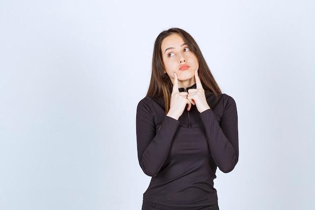 Dziewczyna w czarnych ubraniach wygląda na zamyśloną i wątpliwą.