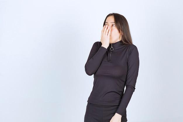 Dziewczyna w czarnych ubraniach wygląda na zaskoczoną i przestraszoną.