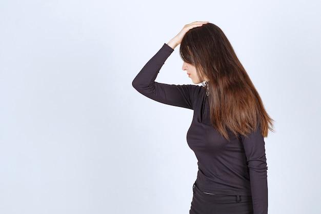 Dziewczyna w czarnych ubraniach wygląda na złą i zdenerwowaną.