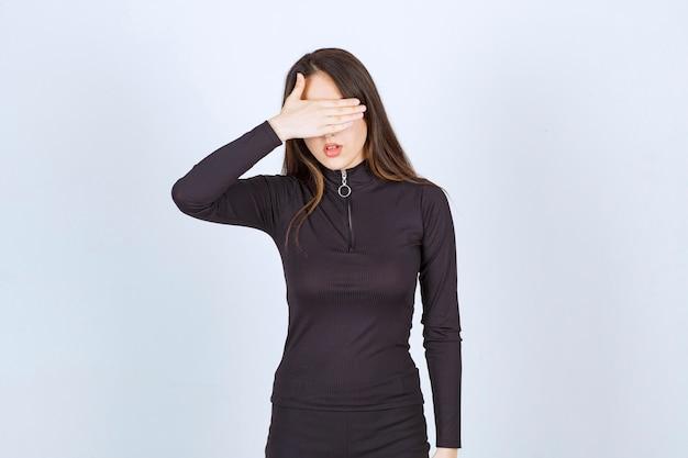 Dziewczyna w czarnych ubraniach zakrywających twarz lub oczy.
