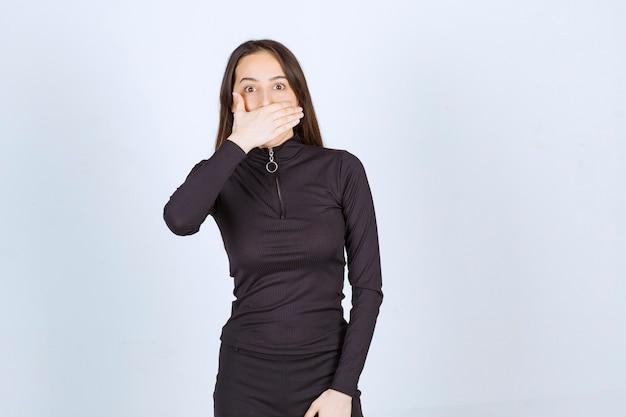 Dziewczyna w czarnych ubraniach zakrywających usta ręką.