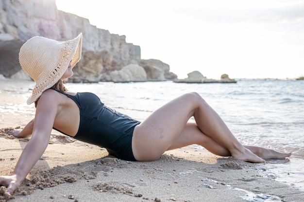 Dziewczyna w czarnym jednoczęściowym kostiumie kąpielowym i słomkowym kapeluszu leży nad brzegiem morza. odpocznij nad morzem w ciepłym kraju.