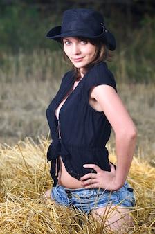 Dziewczyna w czarnym kowbojskim kapeluszu, czarnej koszuli i dżinsowych szortach siedzi na stogu siana
