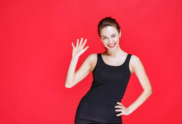 Dziewczyna w czarnym podkoszulku stojąc na czerwonej ścianie i pozdrawiając kogoś.