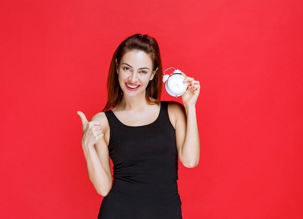 Dziewczyna w czarnym podkoszulku trzymająca budzik i pokazująca pozytywny znak ręki