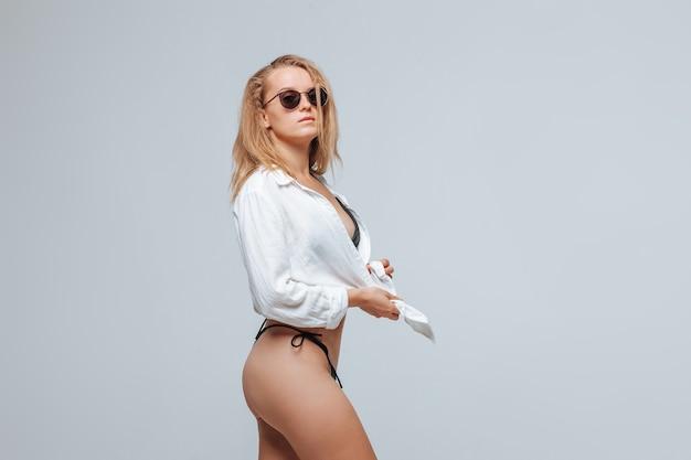 Dziewczyna w czarnym stroju kąpielowym i okularach przeciwsłonecznych i białej koszuli na jasnoszarym tle