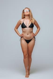 Dziewczyna w czarnym stroju kąpielowym i okularach przeciwsłonecznych na jasnoszarym tle