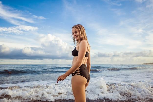 Dziewczyna w czarnym stroju kąpielowym spaceruje wzdłuż oceanu