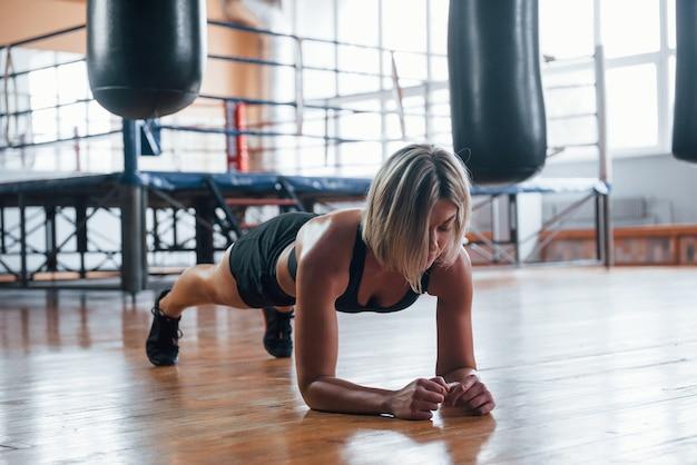 Dziewczyna w czarnym stroju sportowym ma ćwiczenia deski na podłodze sali gimnastycznej.