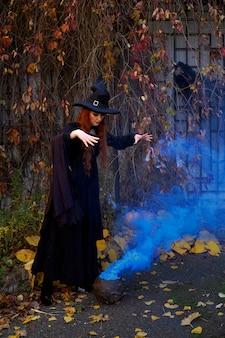 Dziewczyna w czarnym stroju wiedźmy i spiczastym kapeluszu z garnkiem niebieskiego dymu w halloween w jesienny park