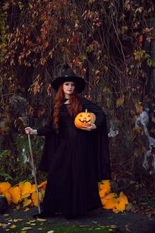 Dziewczyna w czarnym stroju wiedźmy i spiczastym kapeluszu z miotłą i dynią w parku w halloween