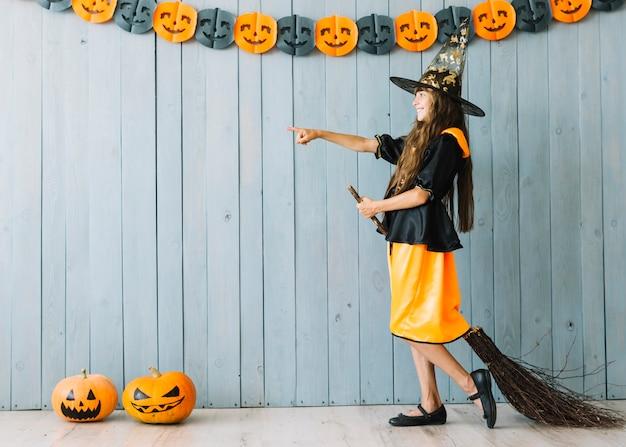 Dziewczyna w czarownica garnitur stojący z miotłą, wskazując od hotelu