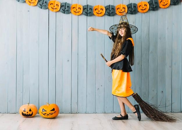 Dziewczyna w czarownica kostiumowa pozycja z miotłą