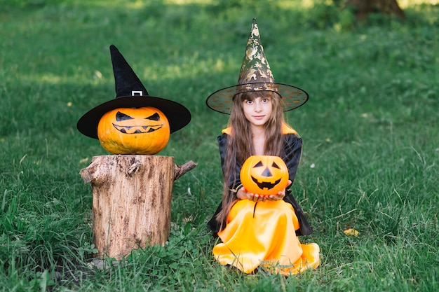 Dziewczyna w czarownica kostiumowym obsiadaniu na trawie blisko bani