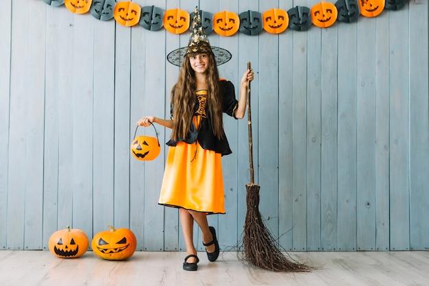 Dziewczyna w czarownica kostiumu trzyma halloweenowego kosz i miotłę