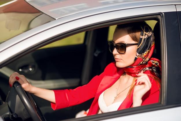 Dziewczyna w czerwieni i okularach przeciwsłonecznych jedzie samochód. dama biznesu w samochodzie, w okularach przeciwsłonecznych