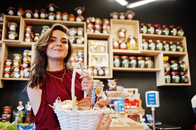 Dziewczyna w czerwieni trzyma różnych produkty na koszu przy delikatesy sklepem.