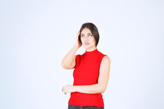 Dziewczyna w czerwonej koszuli co denerwujące i nudne twarz.