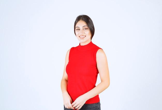 Dziewczyna w czerwonej koszuli dająca piękne i uwodzicielskie pozy.