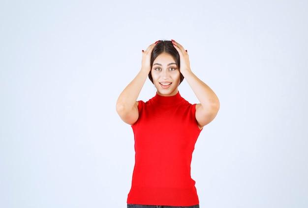 Dziewczyna w czerwonej koszuli dająca pozytywne i uwodzicielskie pozy.