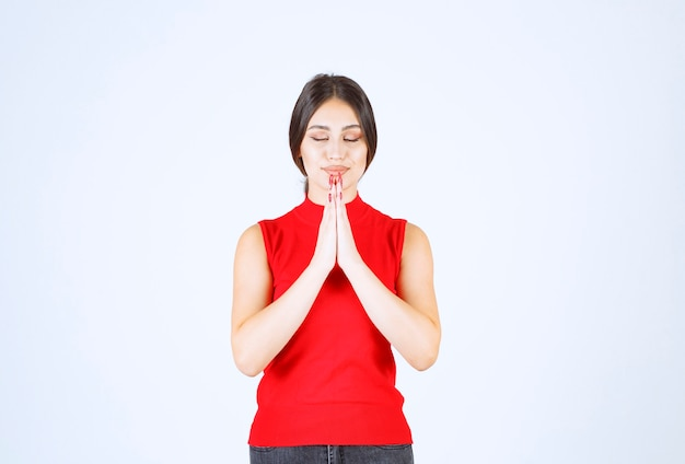 Dziewczyna w czerwonej koszuli jednocząc ręce i modląc się.