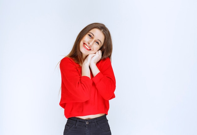 Dziewczyna w czerwonej koszuli jednocząc ręce z wesołą twarzą.