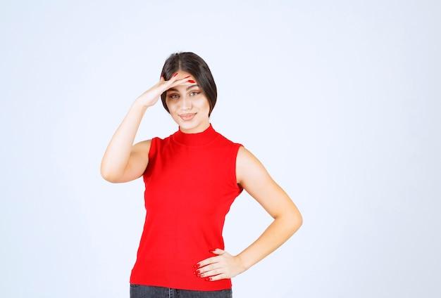 Dziewczyna w czerwonej koszuli, kładąc rękę na czole i czekam.