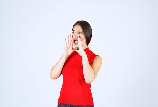 Dziewczyna w czerwonej koszuli krzyczy głośno.