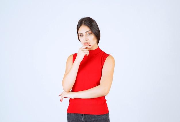 Dziewczyna w czerwonej koszuli myśli i analizuje.