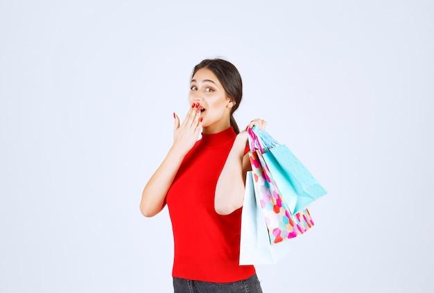 Dziewczyna w czerwonej koszuli niosąc kolorowe torby na zakupy za jej ramieniem.