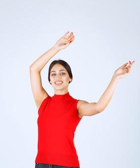 Dziewczyna w czerwonej koszuli podnosząc rękę i wskazując powyżej.